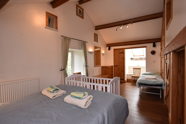 Bedroom 3: with kingsize bed, single bed, wooden floor and en-suite with shower cubicle and toilet.