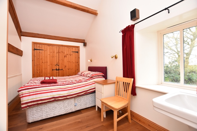 Bedroom 4: with double bed, wooden floor and en-suite with shower cubicle and toilet.