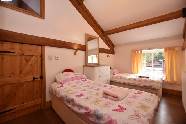 Bedroom 5: with twin beds, wooden floor and en-suite with shower cubicle and toilet.